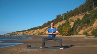 Athletic muscular young man working out, yoga, goddess, sumo wrestler pose