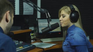 Attractive content radio host interviewing a guest in studio