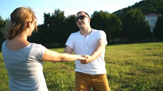 attractive couple holding by hands and whirling on the meadow at leisure