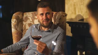 Bearded hipster man drinking wine by the fireplace and flirting with a girl