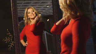 beautiful blonde in red dress posing in the mirror and smiling