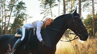 beautiful girl riding on a horse hugging her and stroking