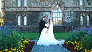 beautiful gorgeous bride and groom walking in sunny park and kissing. happy wedding couple hugging in green garden at old castle