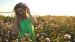 beautiful middle aged blonde woman. attractive sexy girl in a field with flowers posing on camera