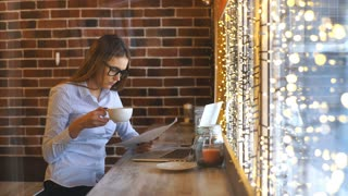 beautiful young businesswoman working in a cafe and studying documents