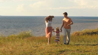 beautiful young family running along the cliff on the background of the river and the sun