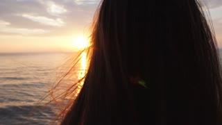 beautiful young woman on the beach watching sunset