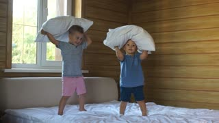 boys fight pillows two brothers play in the bedroom