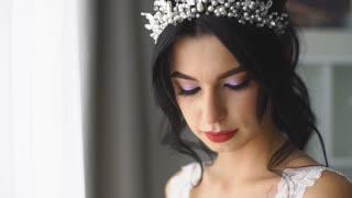 bride with wedding bouquet looks out the window and smiling at camera