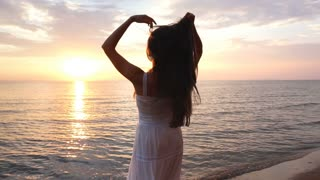 brunette woman with long hair is spinning on the beach at sunset background