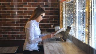 businesswoman working on a computer in a cafe and studying documents