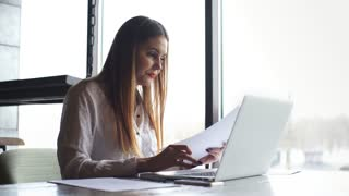 businesswoman working with laptop and checks the documents