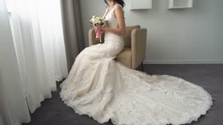 fcae73232 Charming bride in silk robe and veil on her hair is looking at her ...