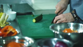 chef hands with knife cutting vegetables on board