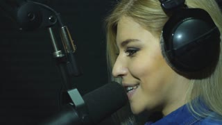 Close-up of happy young female radio host broadcasting in studio