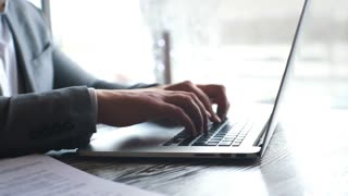 Closeup view of businessman working at sunny office on modern laptop. Male hands typing on notebook keyboard.