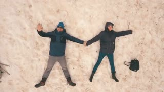 couple lying in the snow,shooting with the drone,Aerial view