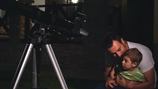 dad and young son looking through a telescope