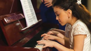family, mother and daughters learn to play piano together in home