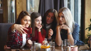 Four beautiful young woman doing selfie in a cafe, best friends girls together having fun