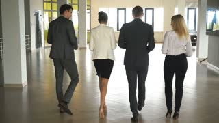 four business people talking and walking in office lobby