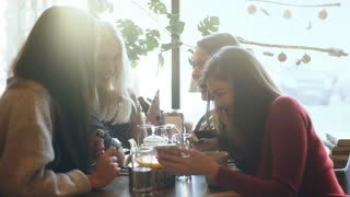 four friends look at the phone and laugh