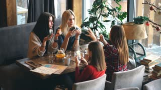 Four woman in cafe using app smartphone playing social network. Technology isolation