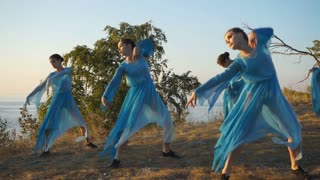 girls in blue dresses dancing on the cliff