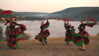 group of girls in bright dresses dancing dance on the hill