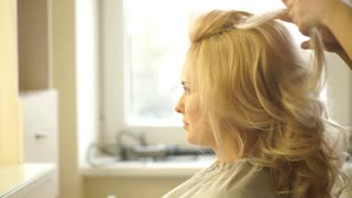 Hairdresser makes evening hairstyle close-up on blond hair of business woman in beauty salon