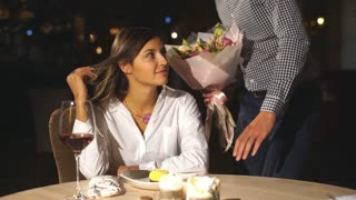 Handsome young man giving present and flowers to beautiful woman in cafe