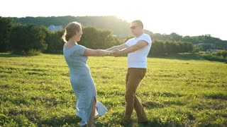 happy couple spinning in a field
