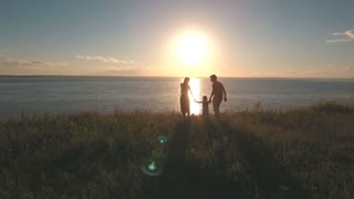 happy mom and dad are on the edge of the cliff and raise her daughter's hands against the sea and sunset