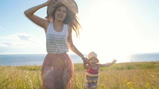 happy mother with little daughter running across the field