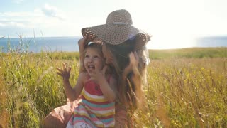 happy mother with little daughter sit in the field and fool around