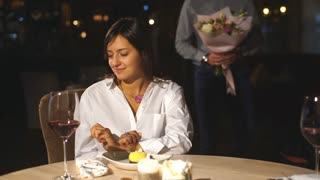 Happy romantic couple in cafe. Young man is presenting flowers to his beloved.
