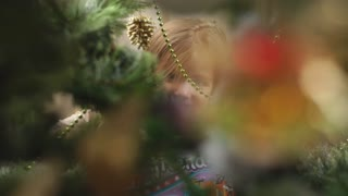 little girl hiding behind Christmas tree