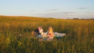 little girl sitting in a field on a blanket