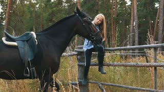 Love and understanding between girl and horse. Redhead girl and brown horse in the forest.