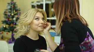 Make-up artist applying lipstick with a brush on model's lips