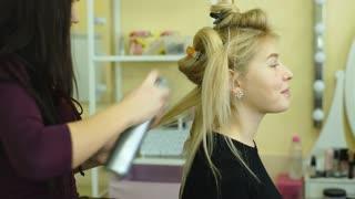 Makeup artist creating beautiful makeup for blonde model
