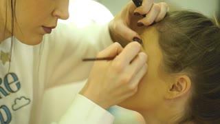 Makeup artist creating beautiful makeup for brunettemodel
