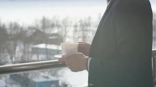 man drinking coffee on the balcony with mountains in the background