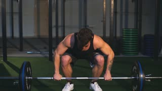 Muscular men lifting deadlift in the crossfit gym