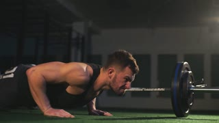 Nice guy with a beard prepares to make a pushup in the gym on the black background