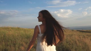 On a sunny day, a woman is walking along a wheat field with a white dress on a nature background