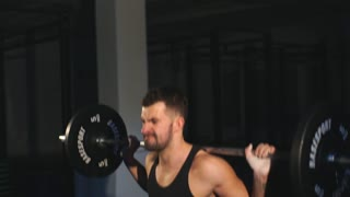 Professional athlete makes squats with a bar in the gym