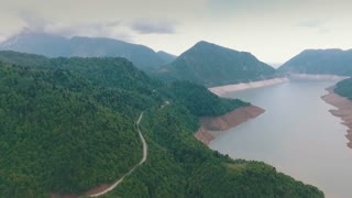 Scenic view of the winding asphalt road along the river, the mountains and the river
