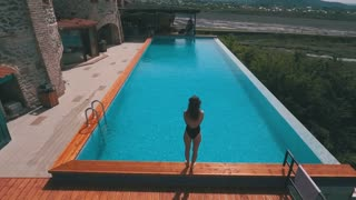 slim woman jumping into the pool