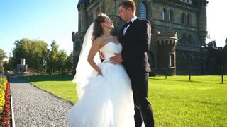 Sophisticated bride and groom kissing near castle. Wedding couple walking in oldest castle